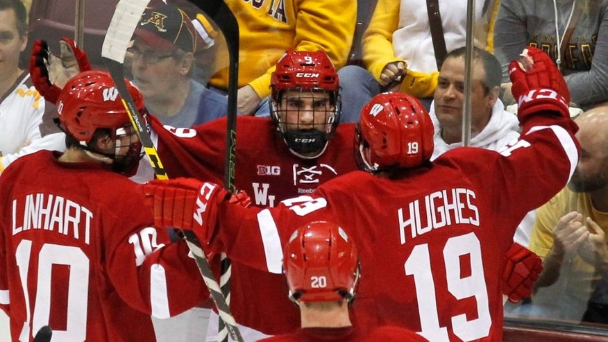 Wisconsin forward Luke Kunin (9) is congratulated by teammates Jake Linahrt and Cameron Hughes after scoring a goal against Minnesota in the first period of an NCAA college hockey game, Friday, March 11, 2016, in Minneapolis.(AP Photo/Andy Clayton-King)
