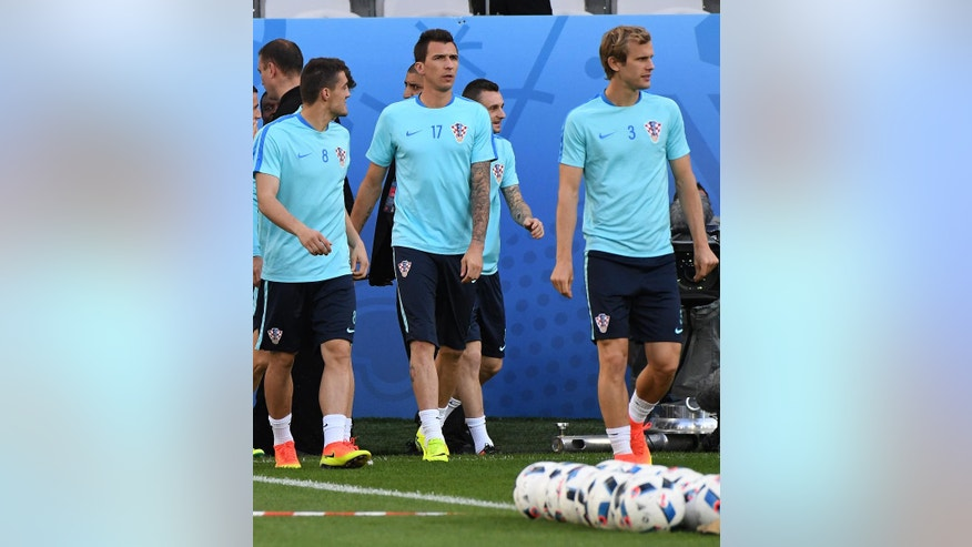 Croatia's Mario Mandzukic, center, attends a training session at the Bollaert-Delelis stadium in Lens, France, Friday, June 24, 2016. Croatia faces Portugal in a round of 16 soccer match on Saturday, June 25,2016. (AP Photo/Geert Vanden Wijngaert)