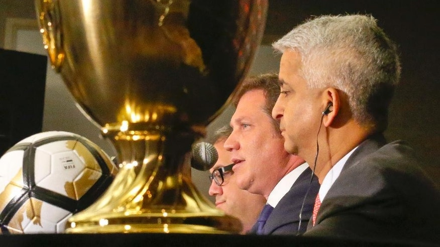 U.S. Soccer Federation President Sunil Gulati, right,  CONMEBOL President Alejandro Dominguez, center, and CONCACAF President Victor Montagliani hold a press conference with the Copa America Centenario championship trophy on display, Friday, June 24, 2016, in New York. The final between Argentina and Chile is set on Sunday, June 26 at MetLife Stadium in East Rutherford, N.J. (AP Photo/Bebeto Matthews)