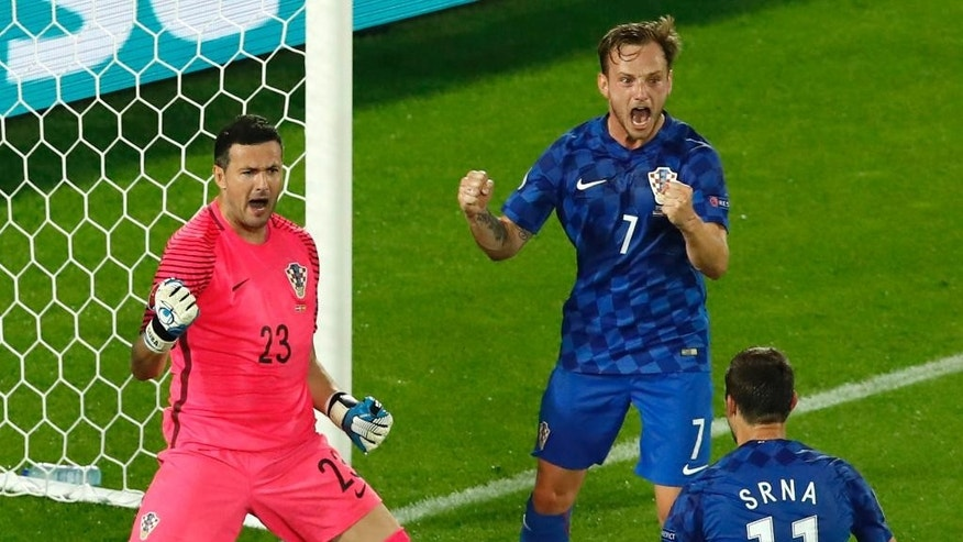 Croatia goalkeeper Danijel Subasic reacts next to Ivan Rakitic after stoping a penalty kick from Spain's Sergio Ramos during the Euro 2016 Group D soccer match between Croatia and Spain at the Nouveau Stade in Bordeaux, France, Tuesday, June 21, 2016. (AP Photo/Andrew Medichini)