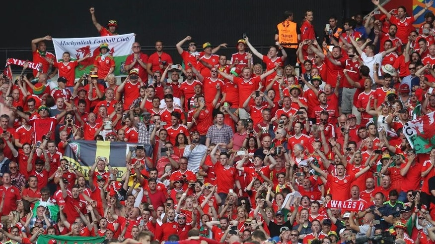 Wales fans cheers in front of the team after Wales wont he Euro 2016 round of 16 soccer match between Wales and Northern Ireland, at the Parc des Princes stadium in Paris, Saturday, June 25, 2016. Wales beat Northern Ireland 1-0. (AP Photo/Petr David Josek)