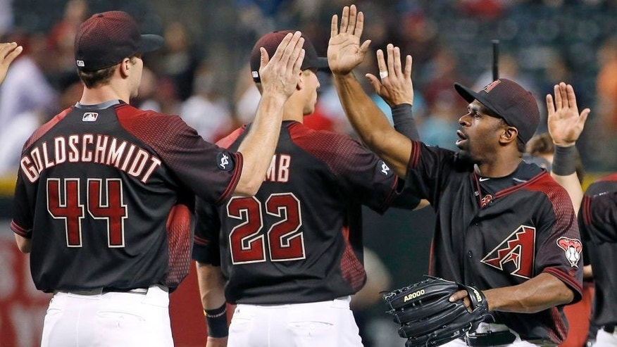Arizona Diamondbacks' Michael Bourn, right, high-fives with Jake Lamb (22) and Paul Goldschmidt (44) after the final out in the ninth inning of a baseball game against the San Diego Padres Saturday, May 28, 2016, in Phoenix. The Diamondbacks defeated the Padres 8-7. (AP Photo/Ross D. Franklin)
