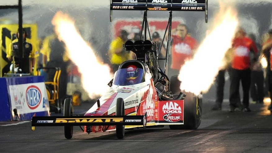 In this photo provided by NHRA, Doug Kalitta drives in Top Fuel qualifying, in which he set the provisional pole with a run of 3.719 seconds at 327.51 mph at the Summit Racing Equipment NHRA Nationals drag races Friday night, June 24, 2016, in Norwalk, Ohio. (Marc Gewertz/NHRA via AP)