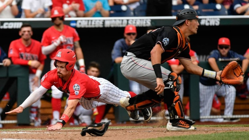 Arizona's Louis Boyd, left, dives safely into home plate to score on a double by Zach Gibbons as Oklahoma State catcher Collin Theroux, right, waits for the ball during the fourth inning of an NCAA men's College World Series baseball game in Omaha, Neb., Saturday, June 25, 2016. (AP Photo/Ted Kirk)