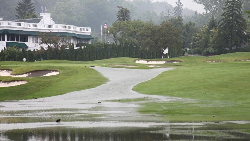 This Thursday June 23, 2016 image provided by the Greenbrier shows flooding on a fairway in front of the clubhouse of the Old White Course at the Greenbrier in White Sulphur Springs, W. Va. Severe flooding hit the area that is scheduled to host a PGA tour event in two weeks. (Harry Watson/The Greenbrier via AP)
