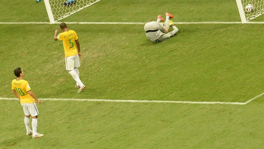 Brazil's goalkeeper Julio Cesar (R) fails to save a goal as Brazil's midfielder Fernandinho (C) and Brazil's midfielder Hernanes react during the third place play-off football match between Brazil and Netherlands during the 2014 FIFA World Cup at the National Stadium in Brasilia on July 12, 2014. AFP PHOTO / EVARISTO SA