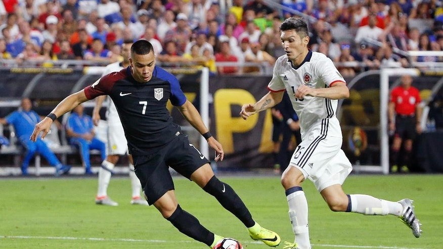 United States' Bobby Wood (7) tries to shoot as Colombia's Daniel Torres (16) arrives to defend during the second half of the Copa America Centenario third-place soccer match Saturday, June 25, 2016, in Glendale, Ariz. (AP Photo/Ross D. Franklin)