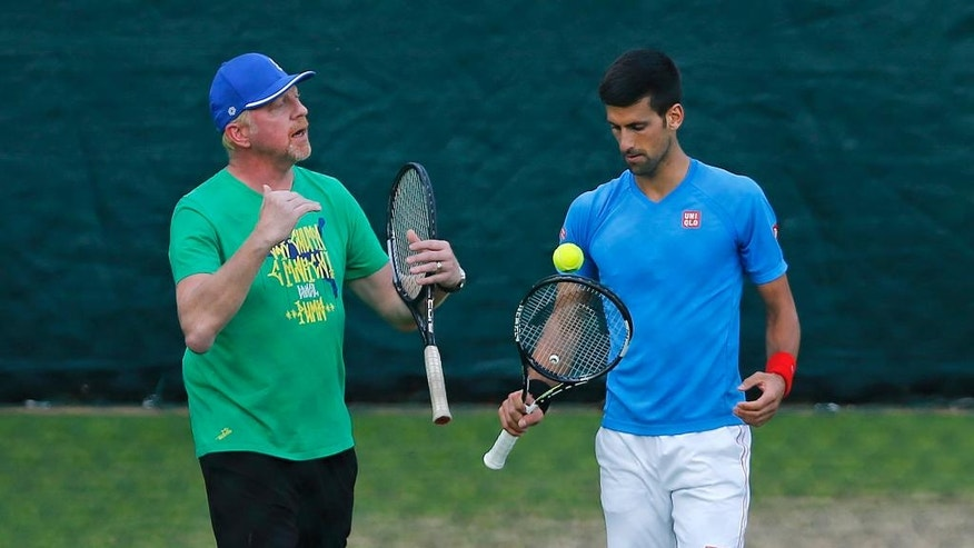 Novak Djokovic of Serbia is coached by Boris Becker, left, during a training session the day before the Wimbledon Tennis Championships in London,  Sunday, June 26, 2016. (AP Photo/Ben Curtis)