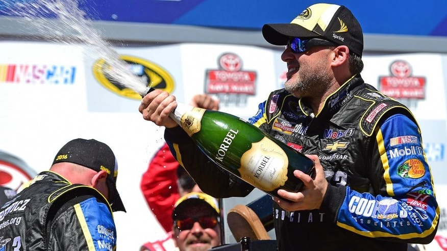 SONOMA, CA - JUNE 26: Tony Stewart, driver of the #14 Code 3 Assoc/Mobil 1 Chevrolet, celebrates with champagne in victory lane after winning the NASCAR Sprint Cup Series Toyota/Save Mart 350 at Sonoma Raceway on June 26, 2016 in Sonoma, California. (Photo by Jared C. Tilton/Getty Images)