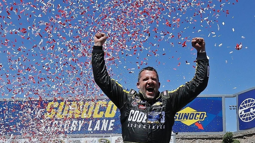 Tony Stewart celebrates after winning the NASCAR Sprint Cup Series auto race Sunday, June 26, 2016, in Sonoma, Calif. (AP Photo/Ben Margot)