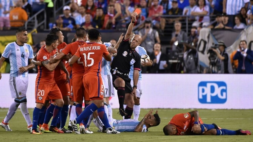 Brazilian referee Heber Lopes red-cards Argentina's Marcos Rojo (C on the ground) for fouling Chile's Arturo Vidal (R on the ground) the Copa America Centenario final in East Rutherford, New Jersey, United States, on June 26, 2016. / AFP / Nelson ALMEIDA (Photo credit should read NELSON ALMEIDA/AFP/Getty Images)