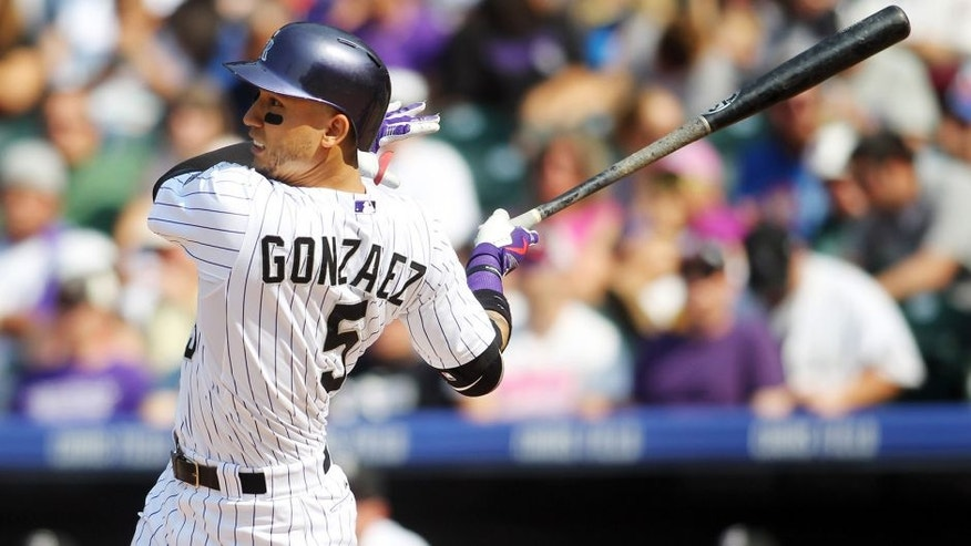 Aug 23, 2015; Denver, CO, USA; Colorado Rockies right fielder Carlos Gonzalez (5) hits a home run during the fourth inning against the New York Mets at Coors Field. The Mets won 5-1. Mandatory Credit: Chris Humphreys-USA TODAY Sports