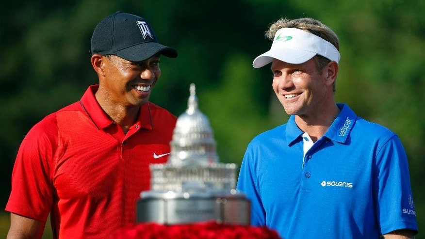 Billy Hurley III, right, chats with Tiger Woods before receiving a trophy for winning the Quicken Loans National PGA golf tournament, Sunday, June 26, 2016, in Bethesda, Md. (AP Photo/Patrick Semansky)