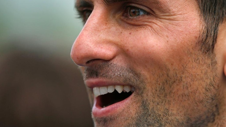 Novak Djokovic of Serbia smiles after completing a training session the day before the Wimbledon Tennis Championships in London,  Sunday, June 26, 2016. (AP Photo/Ben Curtis)