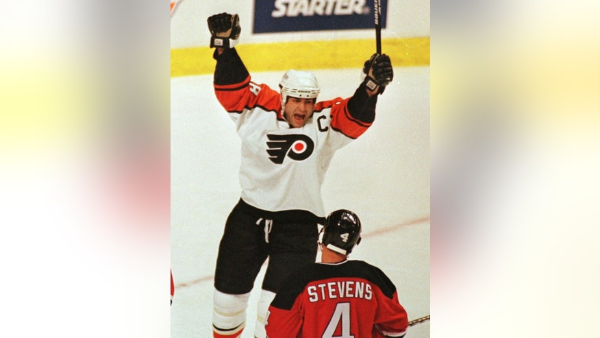 FILE - In this Dec. 10, 1998, file photo, Philadelphia Flyers Eric Lindros reacts after teammate John LeClair scored a goal during the first period as New Jersey Devils Scott Stevens skates past  in Philadelphia. Lindros is finally a Hockey Hall of Famer. Lindros was elected Monday, June 27, 2016, as part of the class of 2016 that also features Soviet star Sergei Makarov and goaltender Rogie Vachon. The late Pat Quinn made it in as a builder. (AP Photo/Chris Gardner, File)