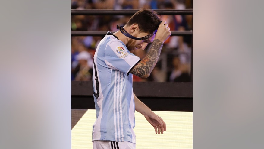 Argentina's Lionel Messi removes his medal after presentations following the Copa America Centenario championship soccer match, Sunday, June 26, 2016, in East Rutherford, N.J. Chile defeated Argentina 4-2 in penalty kicks to win the championship. (AP Photo/Matt Slocum)