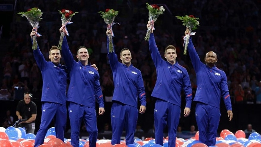 From left, Sam Mikulak, Alex Naddour, Jake Dalton, Chris Brooks and John Orozco wave to the crowd after being named to the U.S. men's Olympic gymnastics team Saturday, June 25, 2016, in St. Louis. (AP Photo/Jeff Roberson)