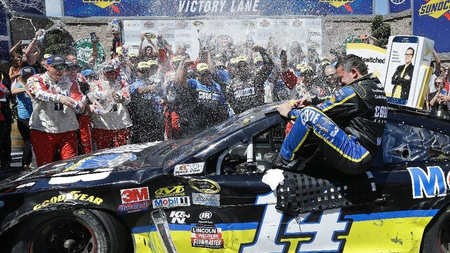 Tony Stewart is sprayed as he climbs out of his car after winning the NASCAR Sprint Cup Series auto race Sunday, June 26, 2016, in Sonoma, Calif. (AP Photo/Ben Margot)