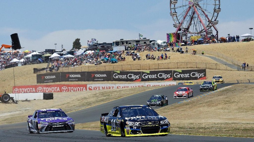 Tony Stewart (14) leads Denny Hamlin, left, race during the NASCAR Sprint Cup Series auto race Sunday, June 26, 2016, in Sonoma, Calif. Stewart won the race, Hamlin finished in second place. (AP Photo/Ben Margot)