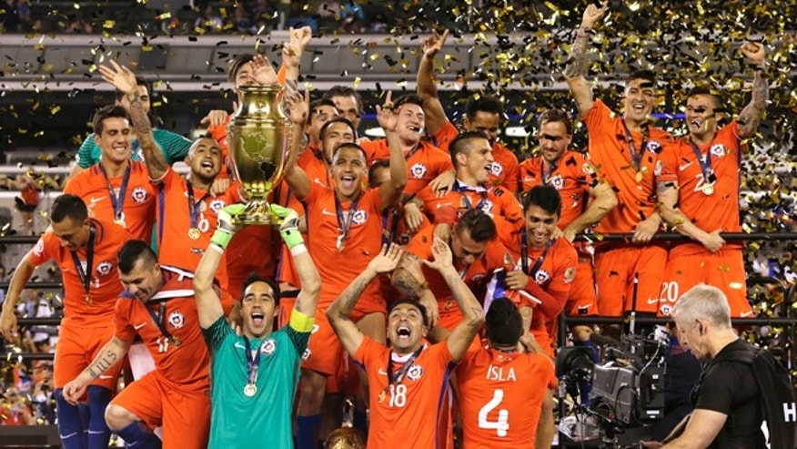 Chile players celebrate with their trophy after the Copa America Centenario championship soccer match, Sunday, June 26, 2016, in East Rutherford, N.J. Chile defeated Argentina 4-2 in penalty kicks to win the championship. (AP Photo/Julio Cortez)