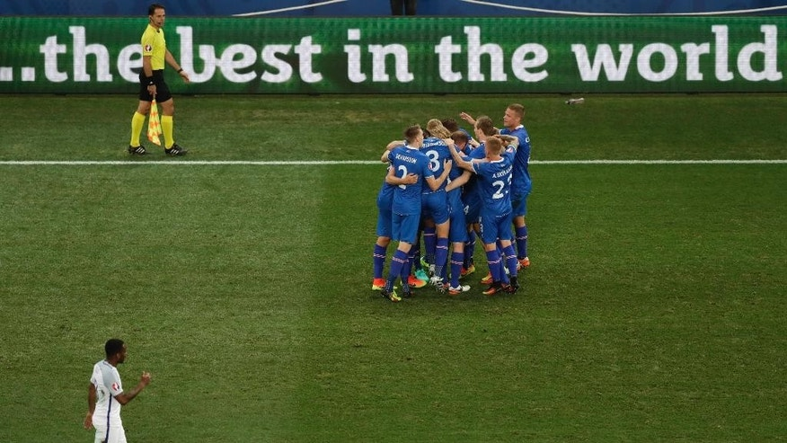 Iceland players congratulate their teammate Kolbeinn Sigthorsson after he scored during the Euro 2016 round of 16 soccer match between England and Iceland, at the Allianz Riviera stadium in Nice, France, Monday, June 27, 2016. On the left below is England's Danny Rose. (AP Photo/Ariel Schalit)