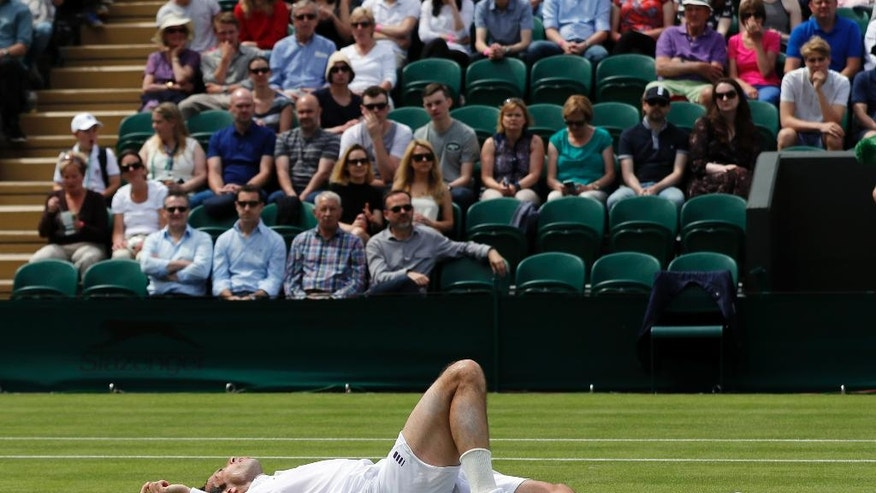 Radek Stepanek of the Czech Republic slips on the grass as he plays Nick Kyrgios of Australia during their men's singles match on day two of the Wimbledon Tennis Championships in London, Tuesday, June 28, 2016. (AP Photo/Ben Curtis)