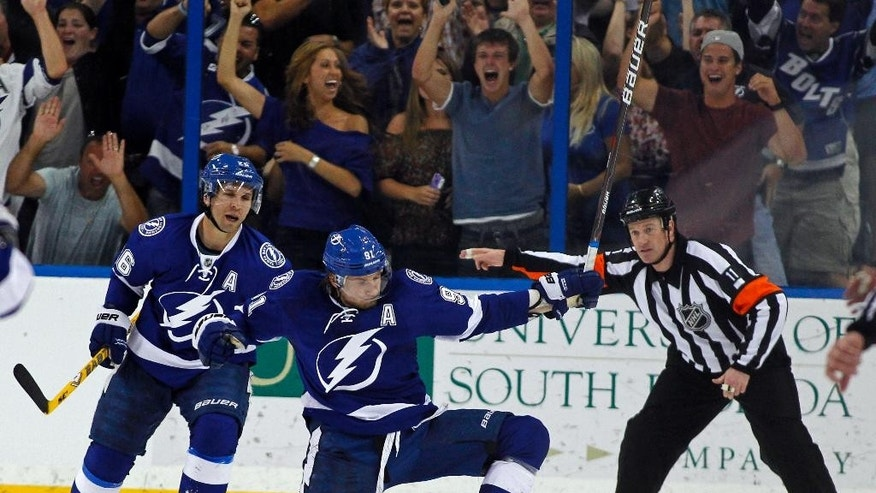 """FILE - In this April 2, 2012, file photo, Tampa Bay Lightning's Steven Stamkos, center, celebrates with teammate Martin St. Louis as referee Kelly Sutherland signals Stamkos' goal during the third period of an NHL hockey game against the Washington Capitals, in Tampa, Fla. Steven Stamkos isn't the only """"big fish"""" available when NHL free agency opens Friday at noon. The top-tier talent is deeper than in many recent years with Milan Lucic, Loui Eriksson, Brian Campbell and others available. (AP Photo/Mike Carlson, File)"""