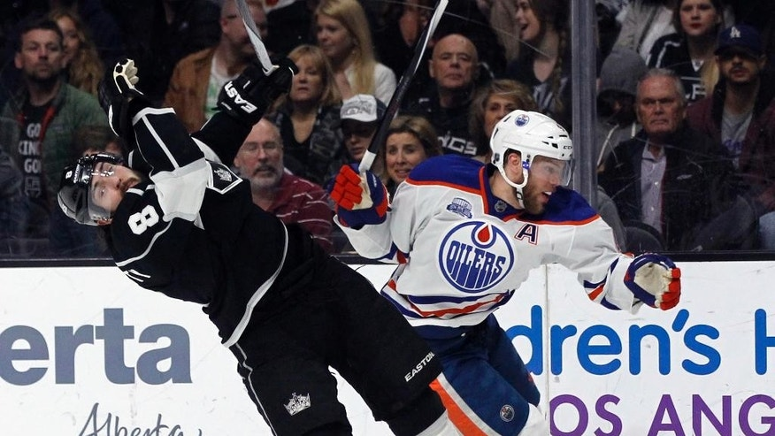 FILE - In this March 26, 2016, file photo, Edmonton Oilers left wing Taylor Hall, right, knocks back Los Angeles Kings defenseman Drew Doughty in pursuit of the puck during the first period of an NHL hockey game in Los Angeles. The New Jersey Devils have acquired former No. 1 overall draft pick Taylor Hall from the Edmonton Oilers for defenseman Adam Larsson. The teams announced the trade Wednesday, June 29, 2016, two days before the start of free agency.  (AP Photo/Alex Gallardo, File)