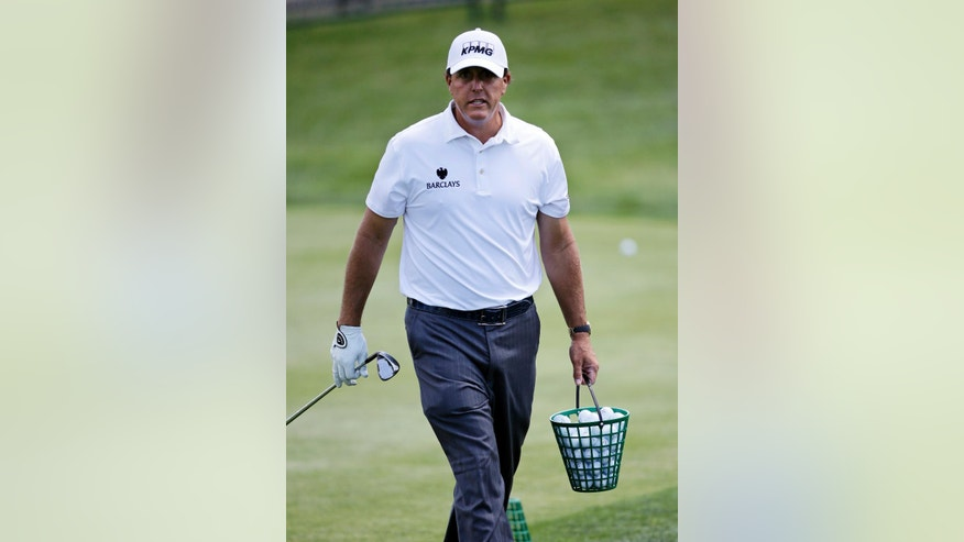 Phil Mickelson walks on the practice range with a bucket of balls during a practice round at the Bridgestone Invitational golf tournament at Firestone Country Club, Wednesday, June 29, 2016, in Akron, Ohio. (AP Photo/Tony Dejak)