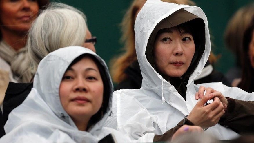 Spectators wait for the match to start as rain delays play on day three of the Wimbledon Tennis Championships in London, Wednesday, June 29, 2016. (AP Photo/Ben Curtis)