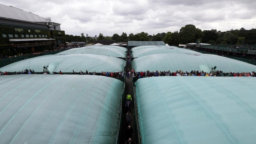Covers are seen on the courts as rain delays play on day three of the Wimbledon Tennis Championships in London, Wednesday, June 29, 2016. (AP Photo/Tim Ireland)