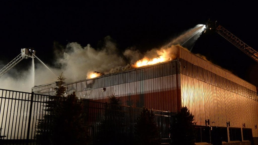 In this June 13, 2016 early morning photo, firemen battle a fire at the ThorSport Racing company's car fabrication shop in Sandusky, Ohio. It's anything but business as usual for ThorSport Racing Team.  (Jilly Burns/Sandusky Register via AP)