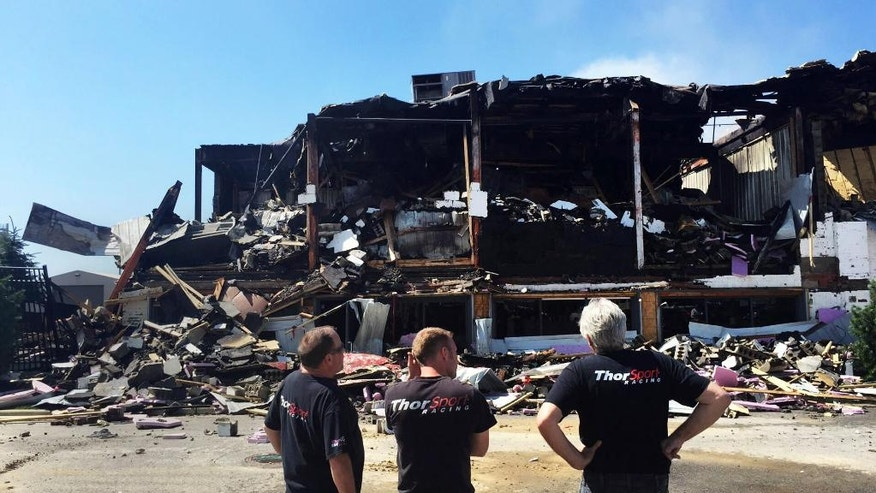 In this June 13, 2016 photo, ThorSport Racing employees survey the damage after a fire at the company's car fabrication shop in Sandusky, Ohio. It's anything but business as usual for ThorSport Racing Team.  (Jilly Burns/Sandusky Register via AP)