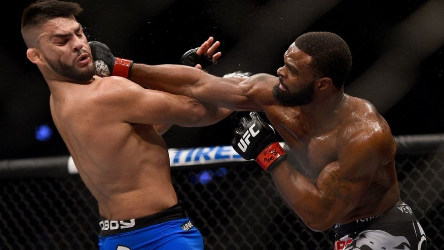 LAS VEGAS, NV - JANUARY 31: (R-L) Tyron Woodley punches Kelvin Gastelum in their welterweight bout during the UFC 183 event at the MGM Grand Garden Arena on January 31, 2015 in Las Vegas, Nevada. (Photo by Jeff Bottari/Zuffa LLC/Zuffa LLC via Getty Images)