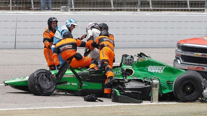 FILE - In this June 12, 2016, file photo, safety workers help Josef Newgarden out of his car after he wrecked with Conor Daly during an IndyCar auto race at Texas Motor Speedway in Fort Worth, Texas. A surgically-repaired right collarbone and broken right wrist couldn't keep Josef Newgarden from his car _ or the debut of his new children's book. (AP Photo/Tim Sharp, File)