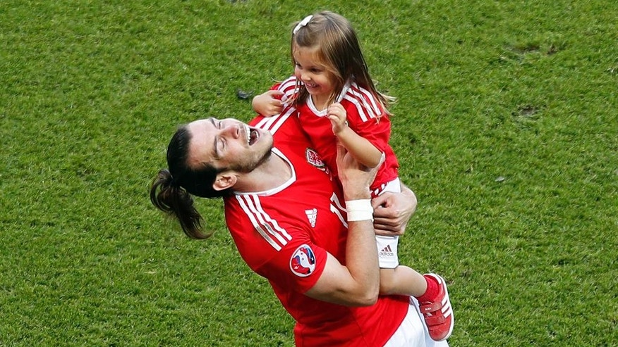 Wales' Gareth Bale celebrates with his daughter Alba after the Euro 2016 round of 16 soccer match between Wales and Northern Ireland, at the Parc des Princes stadium in Paris, Saturday, June 25, 2016. Wales won 1-0. (AP Photo/Francois Mori)