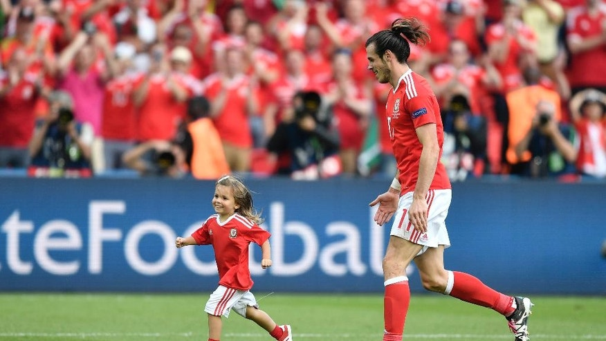 Wales' Gareth Bale celebrates with his daughter Alba after winning the Euro 2016 round of 16 soccer match between Wales and Northern Ireland, at the Parc des Princes stadium in Paris, Saturday, June 25, 2016. (AP Photo/Martin Meissner)