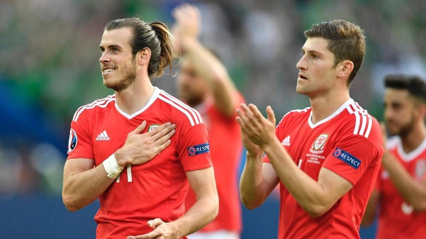 Wales' Gareth Bale, left, celebrates after winning the Euro 2016 round of 16 soccer match between Wales and Northern Ireland, at the Parc des Princes stadium in Paris, Saturday, June 25, 2016. (AP Photo/Martin Meissner)