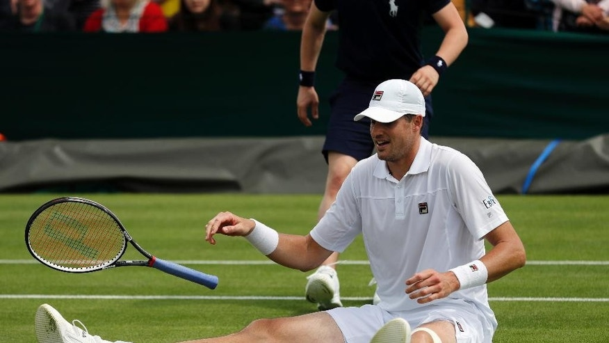 John Isner of the U.S slips and falls as he plays Marcos Baghdatis of Cyprus during their men's singles match on day four of the Wimbledon Tennis Championships in London, Thursday, June 30, 2016. (AP Photo/Ben Curtis)