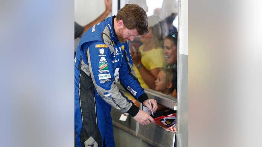 Dale Earnhardt Jr. signs autographs in the garage during a weather delay at NASCAR Sprint Cup auto racing practice at Daytona International Speedway, Thursday, June 30, 2016, in Daytona Beach, Fla. (AP Photo/Wilfredo Lee)
