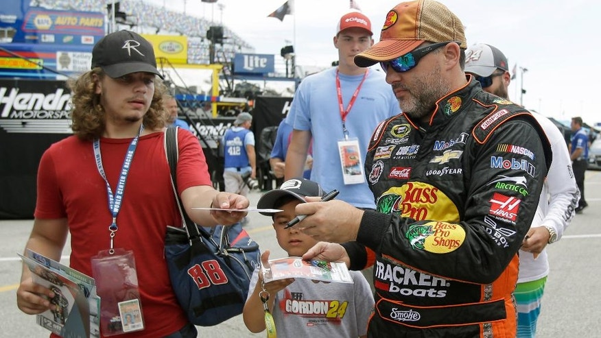 Tony Stewart, right, signs autographs during NASCAR Sprint Cup auto racing practice at Daytona International Speedway, Thursday, June 30, 2016, in Daytona Beach, Fla. (AP Photo/John Raoux)