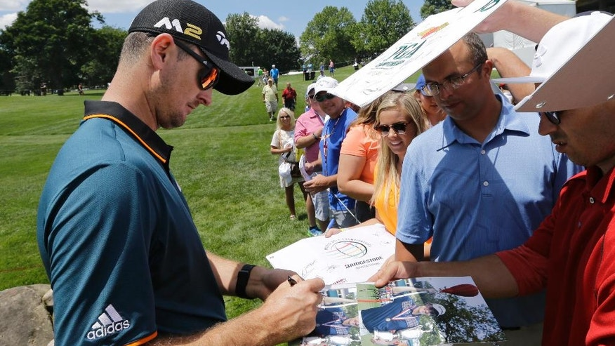 Justin Rose, from England, signs autographs for fans during a practice round at the Bridgestone Invitational golf tournament at Firestone Country Club, Wednesday, June 29, 2016, in Akron, Ohio. (AP Photo/Tony Dejak)