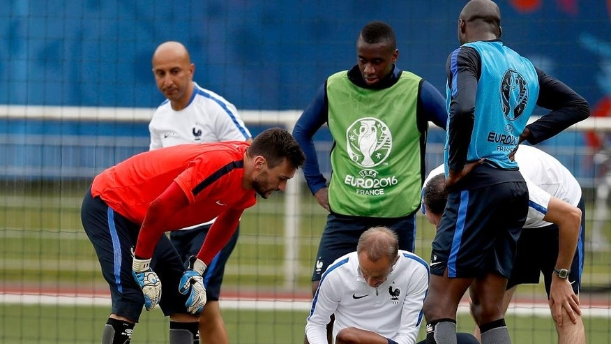 France's Patrice Evra, lies on the pitch as he receives medical treatment after an injury of his left hand during a training session of the national soccer team of France at the Clairefontaine training center, outside Paris, France, Wednesday, June 29, 2016. France will face Iceland in a Euro 2016 quarter final soccer match in Saint-Denis on Sunday, July 3, 2016. (AP Photo/Michael Sohn)