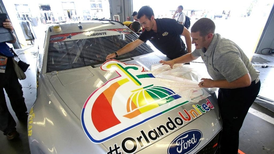Members of the GoFas racing team Mason St. Hilaire, back left, and Timothy Barile apply a decal in support of the victims of the Pulse nightclub shooting to Bobby Labonte's car during a NASCAR Sprint Cup auto racing practice at Daytona International Speedway, Thursday, June 30, 2016, in Daytona Beach, Fla. (AP Photo/John Raoux)