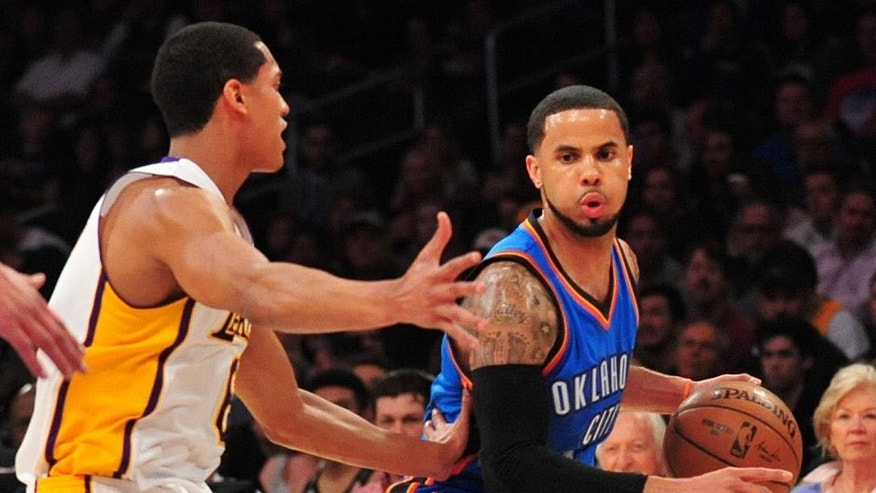 March 1, 2015; Los Angeles, CA, USA; Oklahoma City Thunder guard D.J. Augustin (14) moves the ball against the defense of Los Angeles Lakers guard Jordan Clarkson (6) during the first half at Staples Center. Mandatory Credit: Gary A. Vasquez-USA TODAY Sports