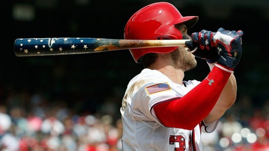 Washington Nationals' Bryce Harper (34) watches his two-run homer as he holds his Independence Day themed bat during the first inning of a baseball game against the San Francisco Giants at Nationals Park, Saturday, July 4, 2015, in Washington. (AP Photo/Alex Brandon)