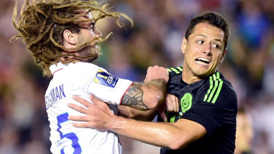 Javier Hernandez of Mexico collides with Kyle Beckerman of the US during their 2015 CONCACAF Cup match at the Rose Bowl in Pasadena, California on October 10, 2015. The match is a playoff for the 2017 Confederations Cup. AFP PHOTO / FREDERIC J. BROWN (Photo credit should read FREDERIC J. BROWN/AFP/Getty Images)