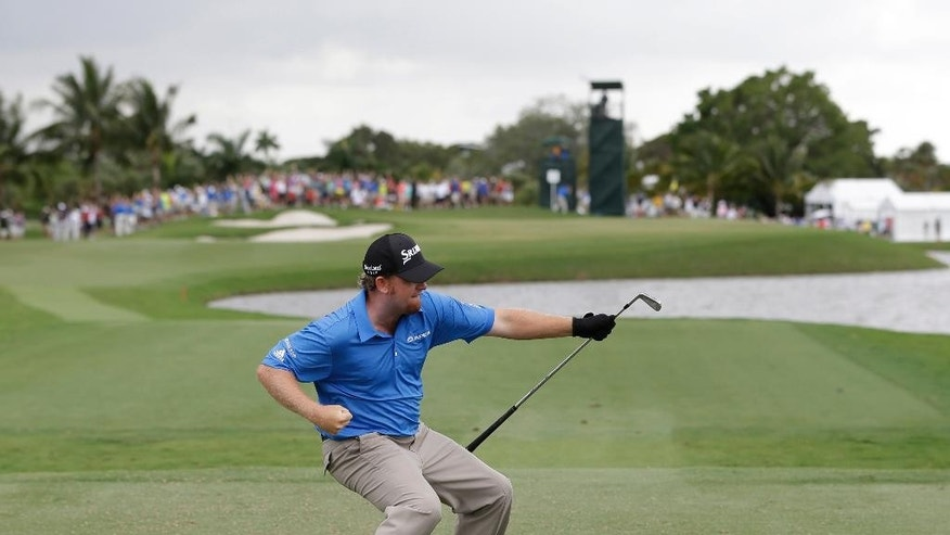 FILE - In this March 7, 2015, file photo, J. B. Holmes celebrates a hole-in-one on the fourth tee during the third round of the Cadillac Championship golf tournament, in Doral, Fla. Every club in the bag had a story to tell in 2015, a year on the PGA Tour marked by big wins, clutch shots and frustration that golf so often produces. (AP Photo/Wilfredo Lee, File)