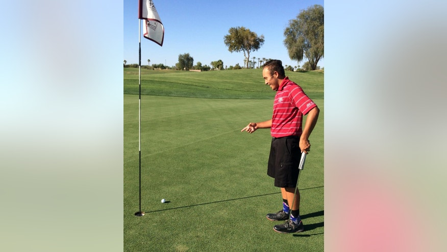 In this photo taken May 13, 2016, Aaron Ramos points to his tee shot on a green at Palm Valley Golf Club in Goodyear, Ariz. Ramos had the closest among 172 shots between six people, including AP Sports Writer John Marshall, as they tried to get an elusive hole-in-one. (AP Photo/John Marshall, File)