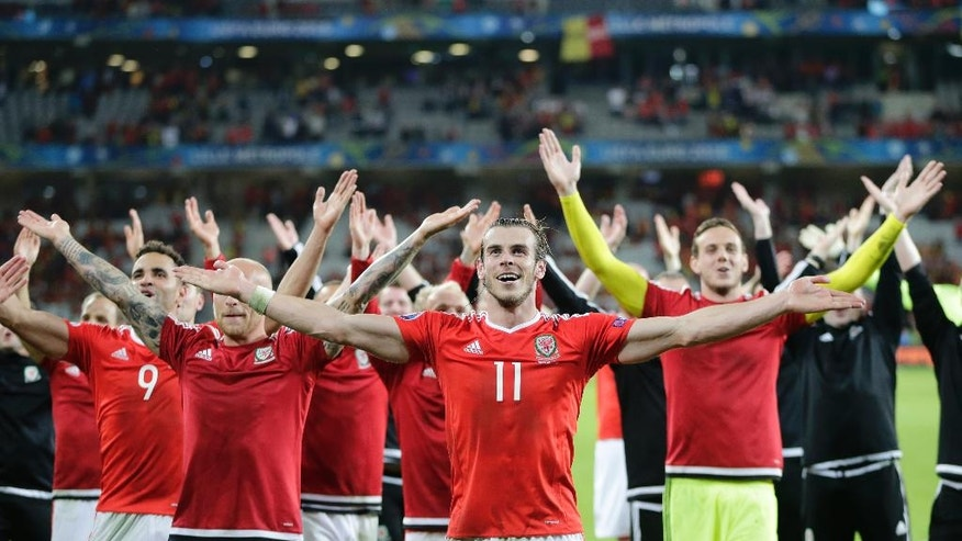 Wales' Gareth Bale, center, celebrates with his teammates after their 3-1 win at the end of the Euro 2016 quarterfinal soccer match between Wales and Belgium, at the Pierre Mauroy stadium in Villeneuve d'Ascq, near Lille, France, Friday, July 1, 2016. (AP Photo/Petr David Josek)